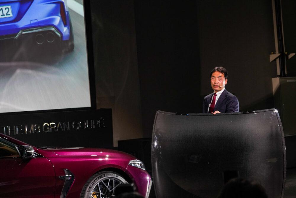 新型BMW M8 グラン クーペ の商品概要をプレゼンする、BMWブランド・マネジメント・ディビジョン プロダクト・マネージャー 御舘 康成氏。カーボンルーフ片手でひょいと持ち上げて見せる。