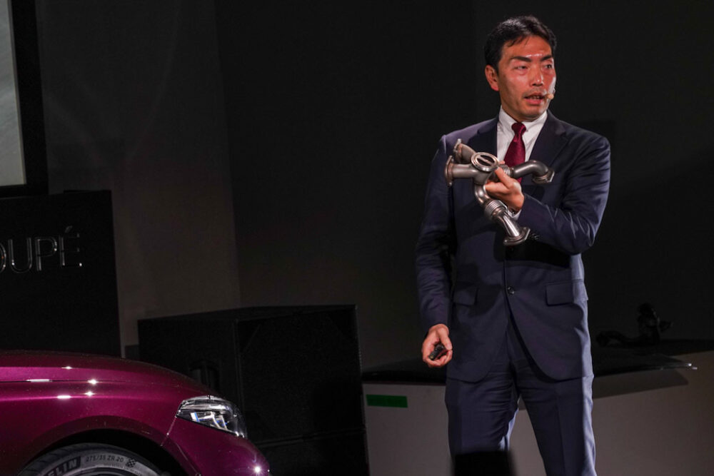 新型BMW M8 グラン クーペの独特な形状をしたエキゾーストマニホールドを手に持って解説する御舘氏。