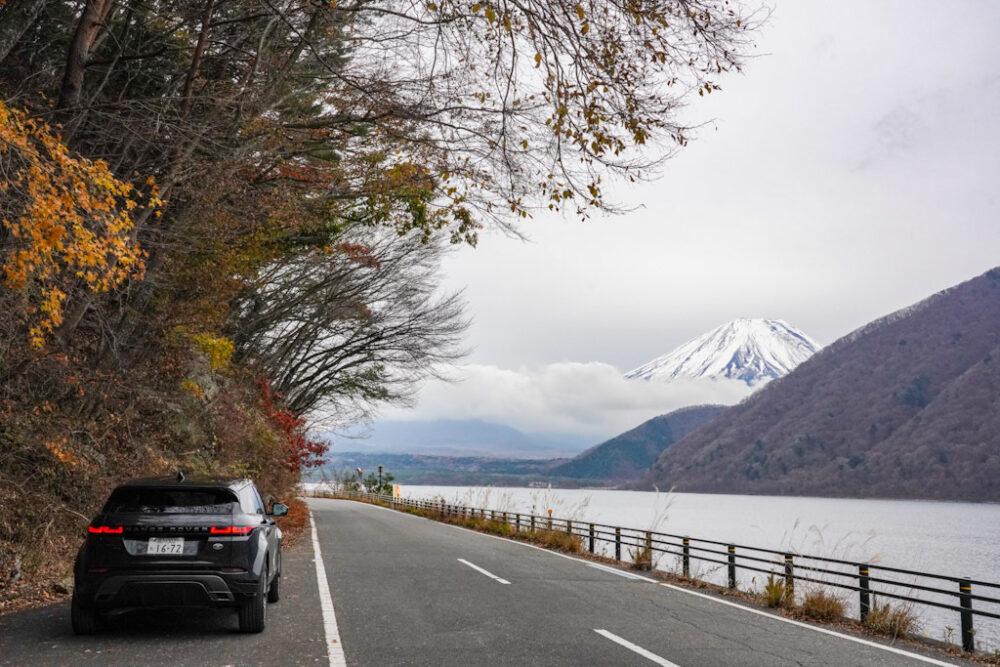 本栖湖畔の道路に停まる新型レンジローバー・イヴォーク R-DYNAMIC HSE P300 MHEV。背景に富士山。