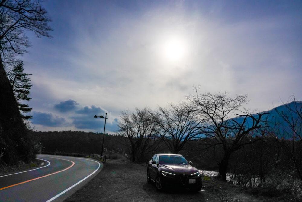 精進湖畔東側の道路。路肩に停まるのはアルファロメオ・ステルヴィオ