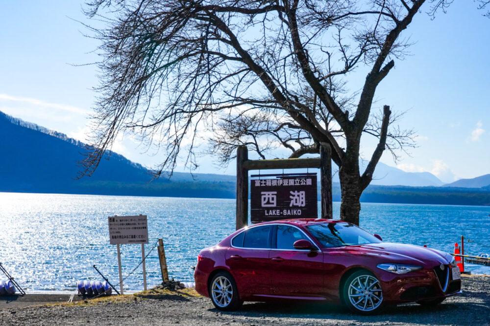 西湖を示す看板。背景は西湖。手前の車両はアルファロメオ・ジュリア・ターボディーゼル