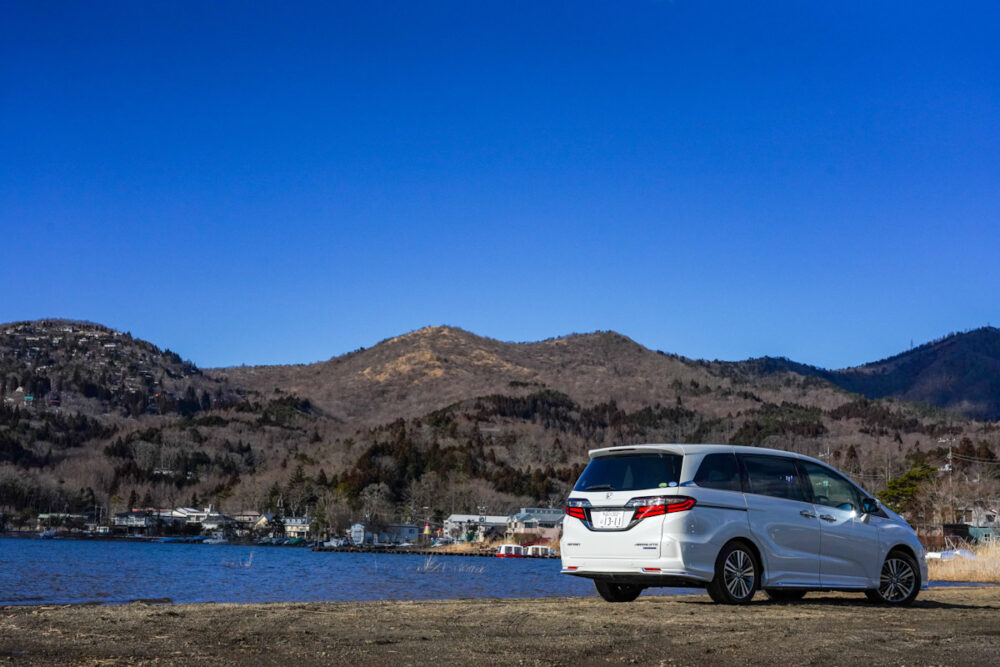 ホンダ オデッセイ ハイブリッド アブソリュート EX HondaSENSING のリア。背景は湖