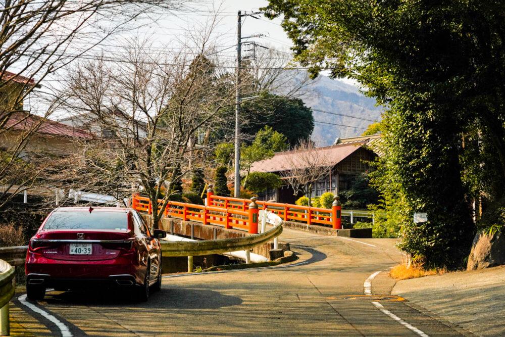 赤い欄干の橋の手前に停まるホンダ レジェンド
