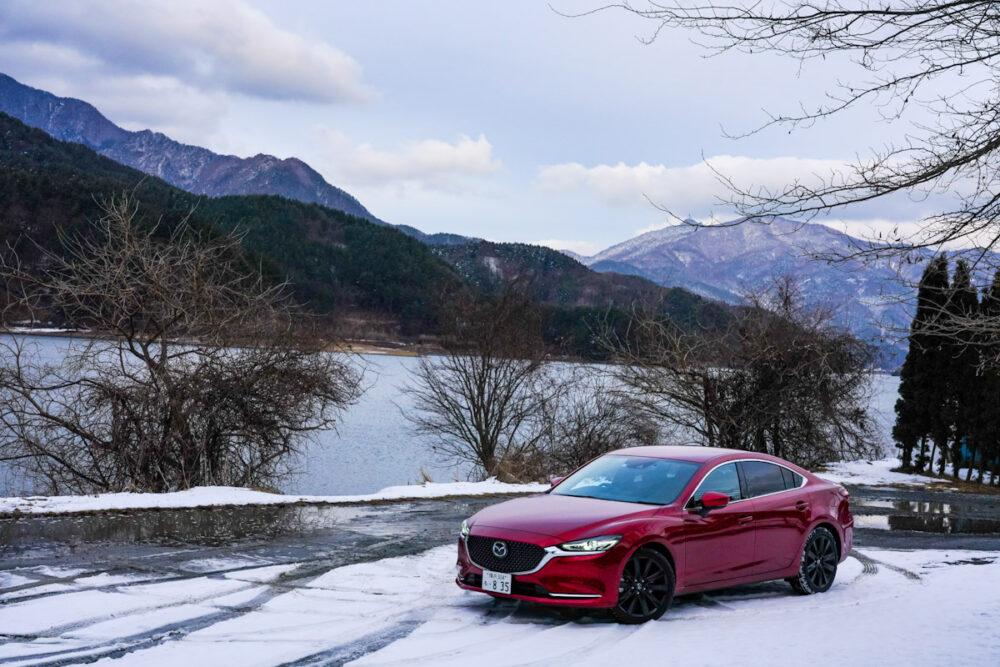 雪の上、湖を背景に停まるマツダ6