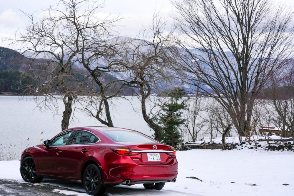 雪の上に停まるマツダ6 のリアを撮影。背景は河口湖