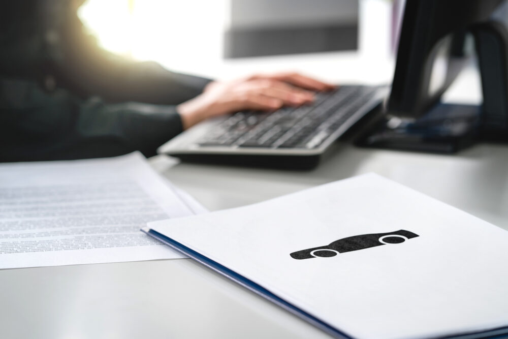 書類とパソコンを触る人の手