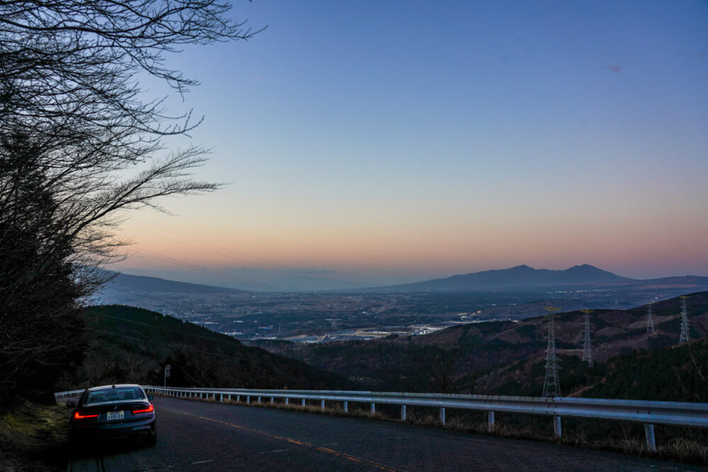 三国峠から御殿場市街を見下ろす。路肩に停まるBMW M340i