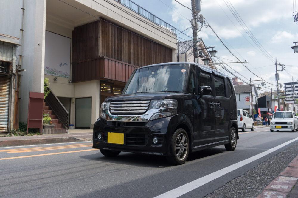 道路を走行する黒の軽自動車