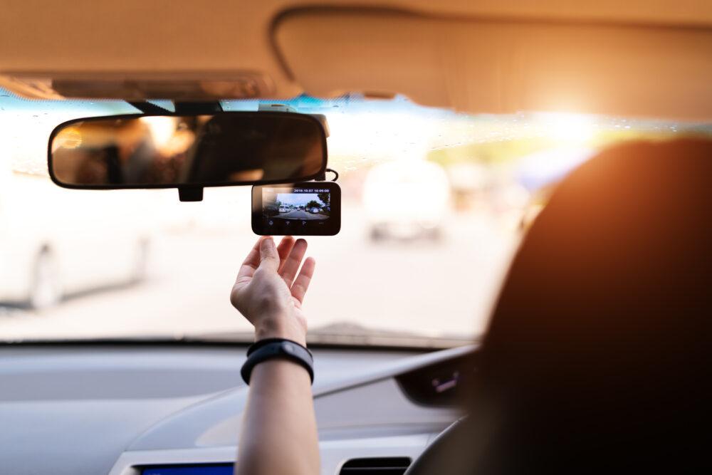 車の運転席でドライブレコーダーを触る女性