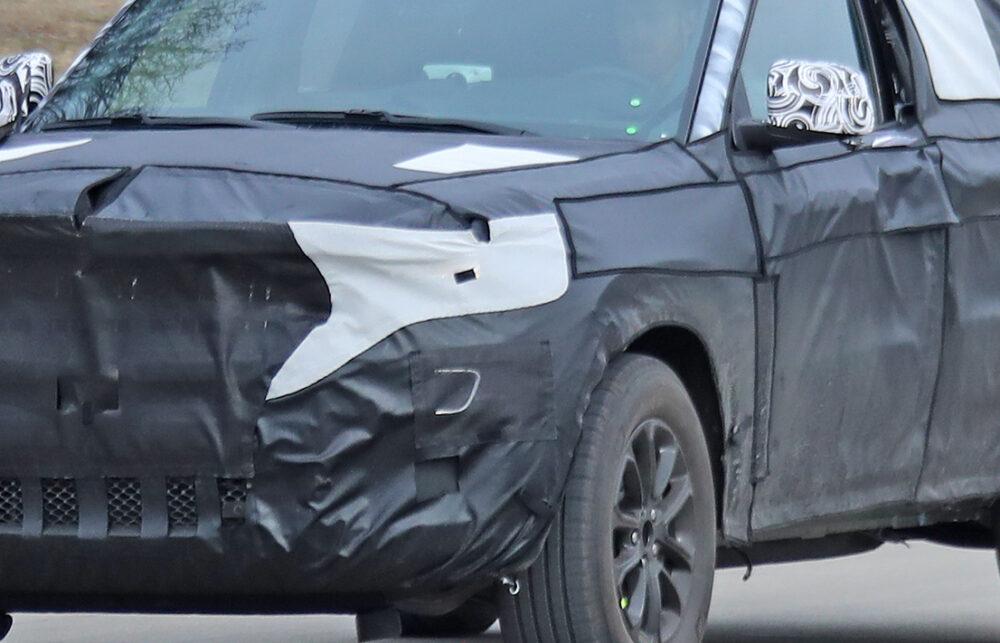 公道を走る次期新型ジープ・グランドチェロキーのプロトタイプ。カモフラージュ柄の塗装の上にシートを貼り付け厳重に隠されている。