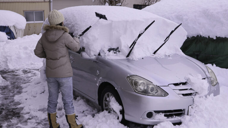 スノーワイパーで自動車の屋根の雪を降ろす女性