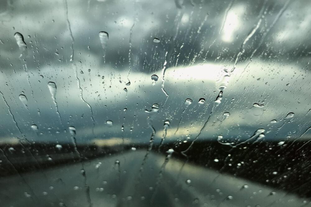 車のフロントガラスを流れる雨水