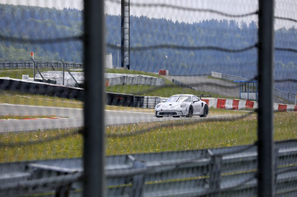 サーキットを走る新型ポルシェ 911 GT3 R プロトタイプ スパイショット コースの金網越しに撮影