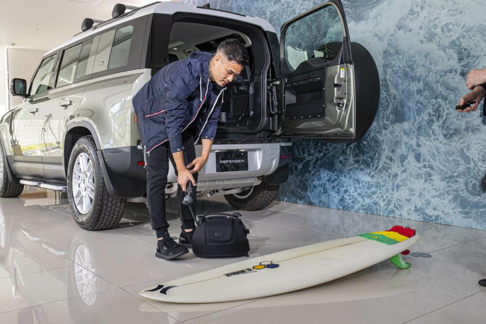 純正オプションの手動ポンプ式シャワーでサーフボードを洗う田村優選手