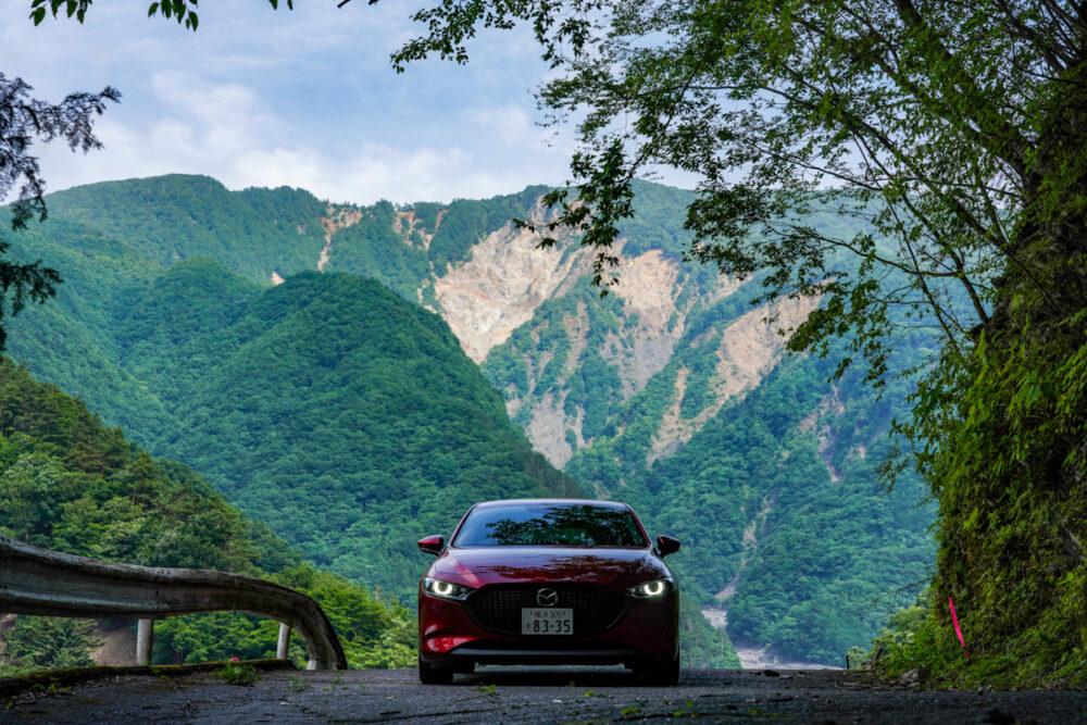マツダ3 ファストバック X MT/AWD 山を背景に撮影