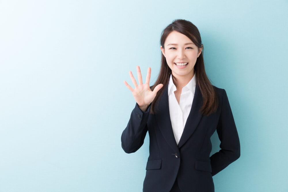 笑顔で手をかざす女性