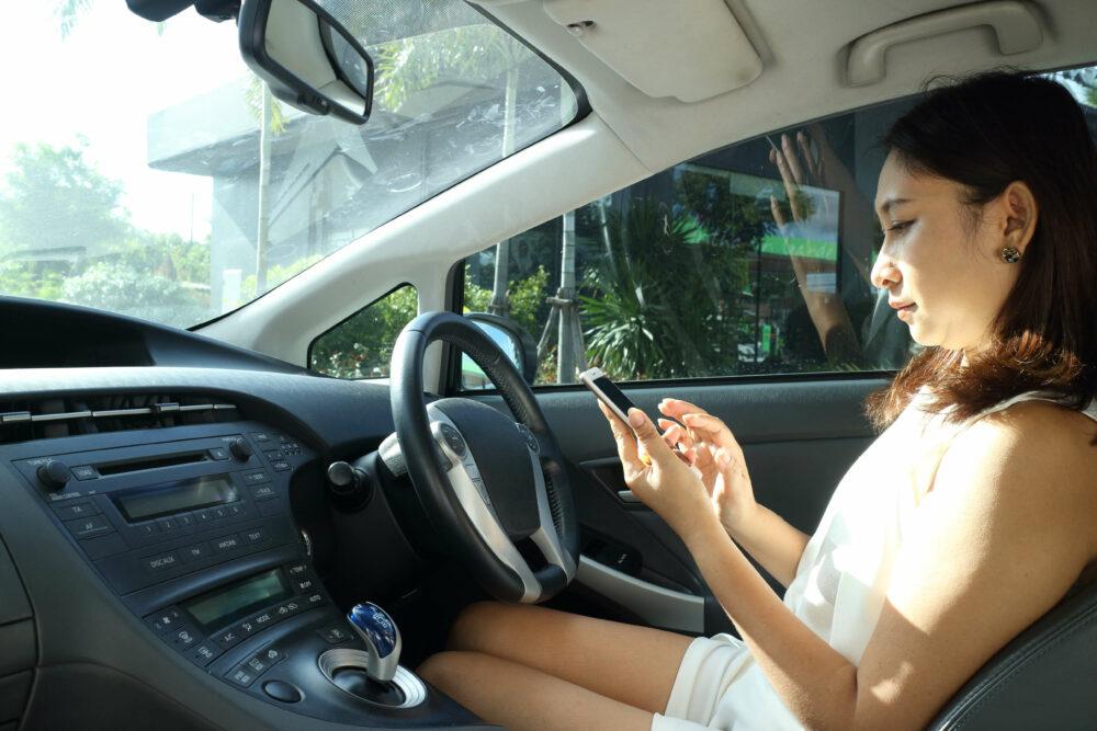 車内で携帯を触る女性