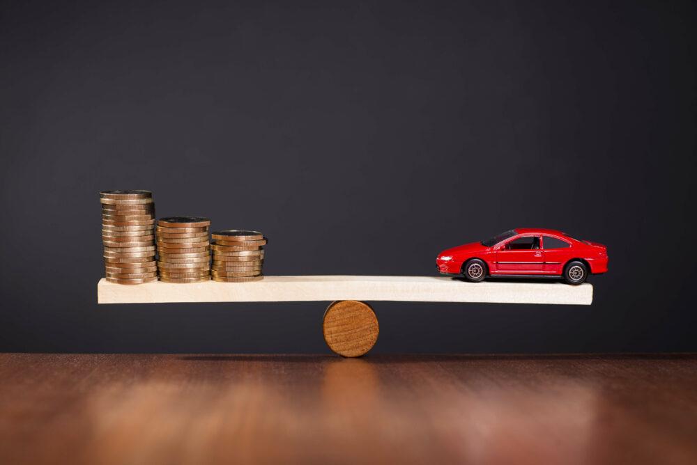 シーソーに乗った車とコインの画像