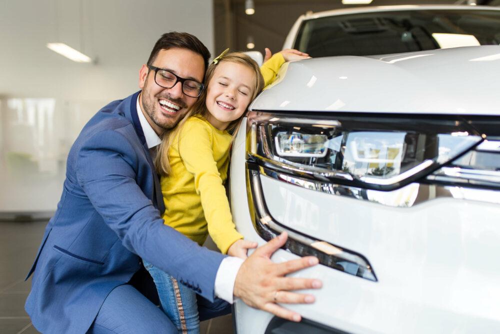 車を買って喜ぶ父と娘