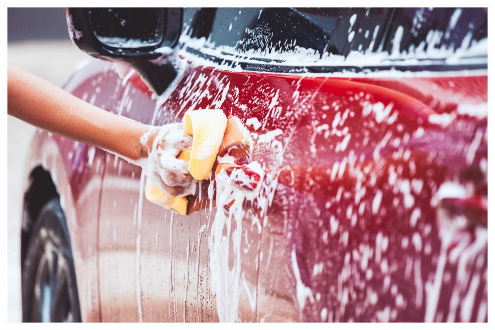 赤い車を洗う人