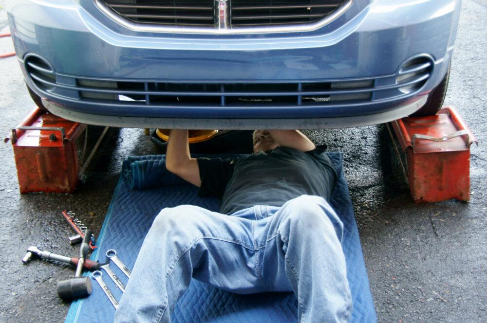 車の下からメンテナンスをする男性