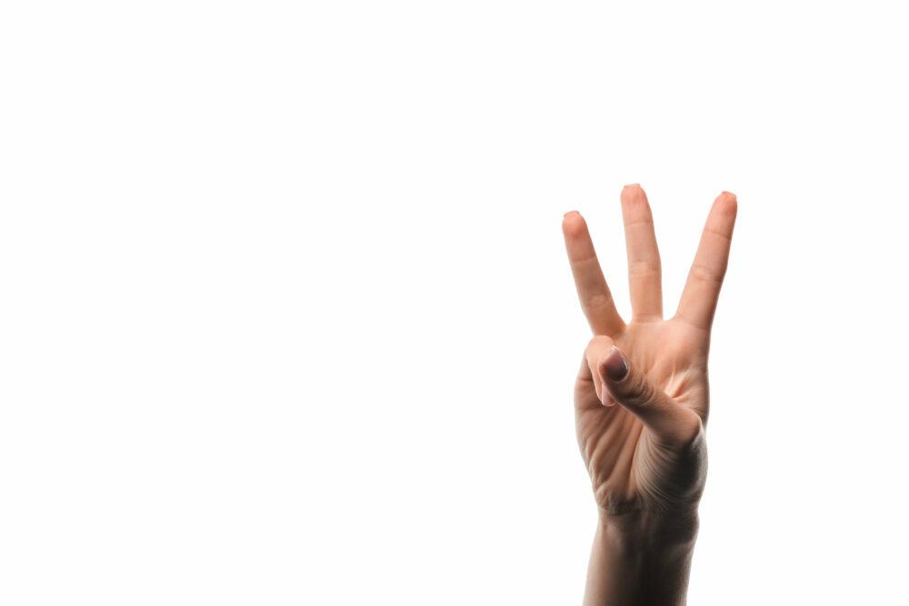 三本指を出す手