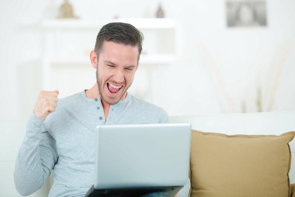 PC画面を見て喜ぶ男性
