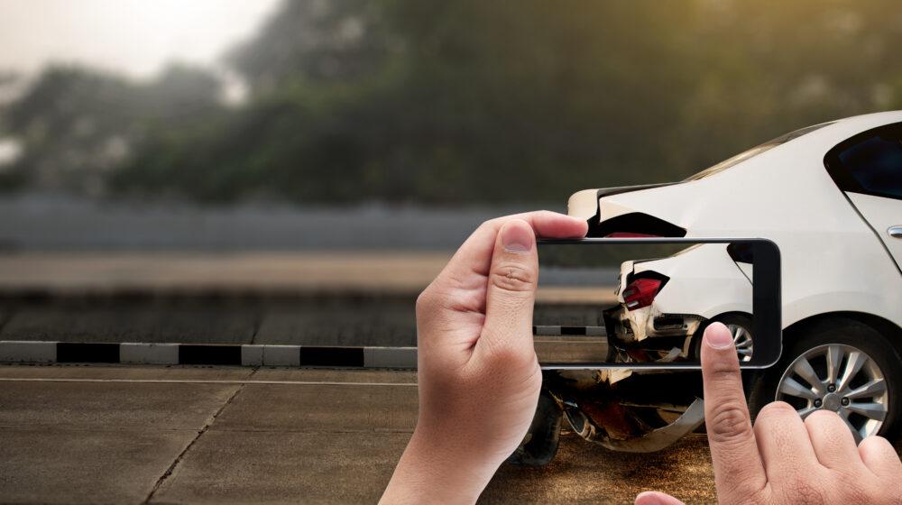 破損した自動車の写真を撮る