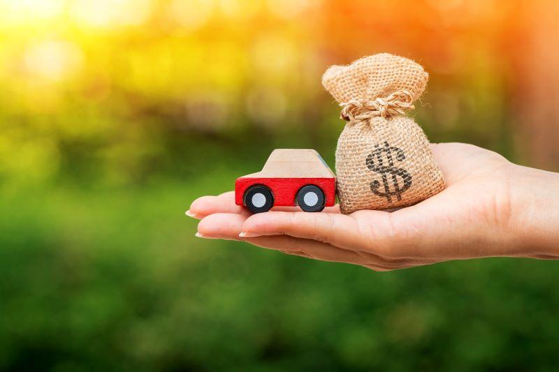 車とお金の袋を持っている手