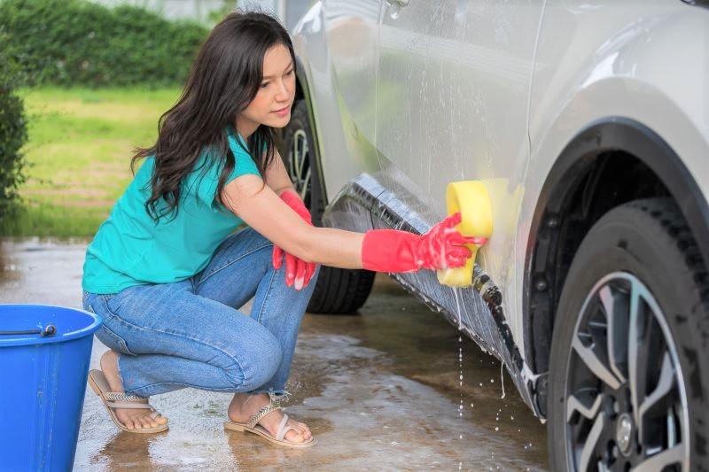 車の洗車をする女性