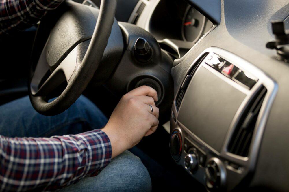 車のイグニッション ロックにキーを挿入する男性のクローズ アップ