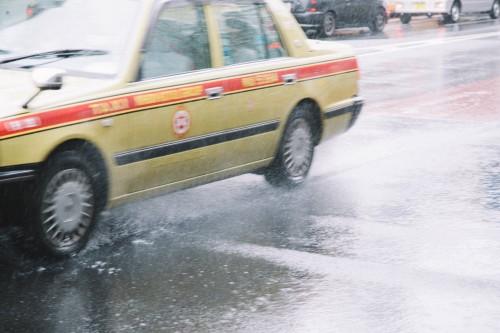 雨の中走るタクシー