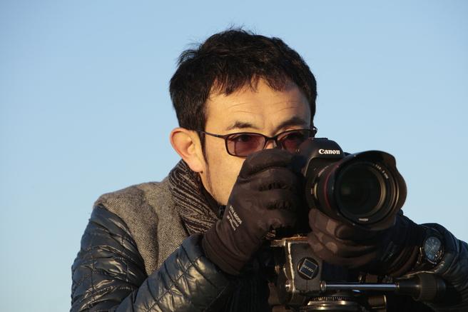 車に向けてカメラを構える郡大二郎